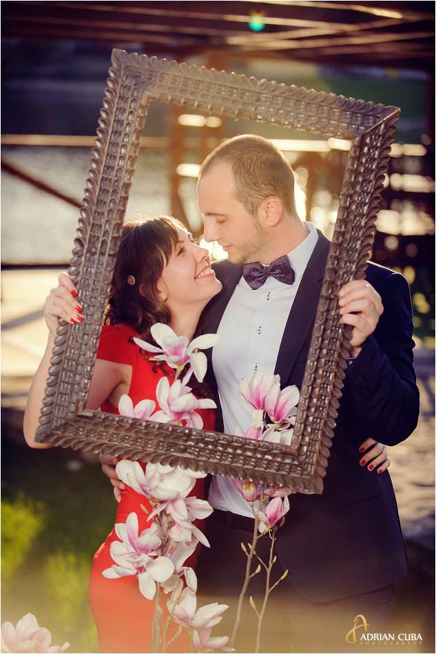 Sesiune foto logodna Iasi, tinerii pozeaza printr-o rama de tablou.